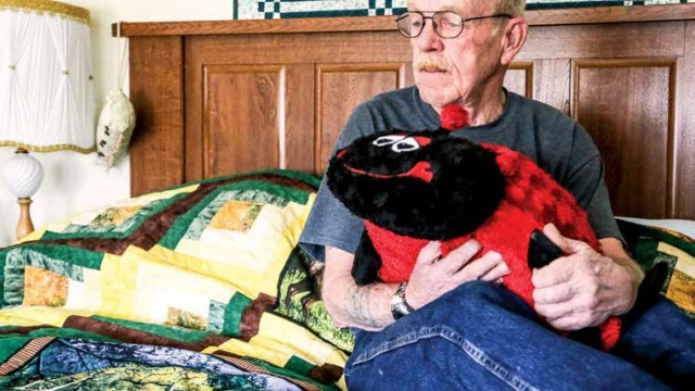 "Jim Cain, Leoda Cain's husband, sits on his side of the bed on the quilt his wife was planning to make before she died. He holds the ""love (lady) bug"" he bought her for Valentine's Day. The bug's place has always been on the bed."