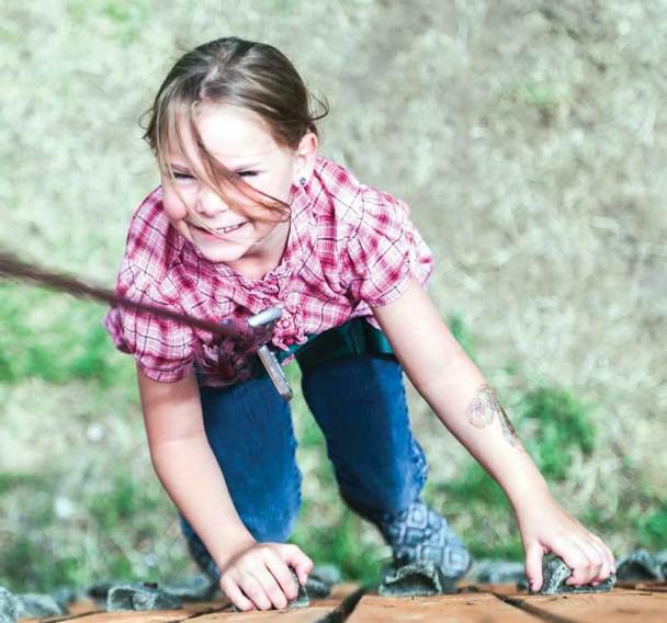 Lydia Hershley, 6, scales a climbing wall at JK Bar Bible Ranch near Glendo on a Boys & Girls Club field trip Friday.
