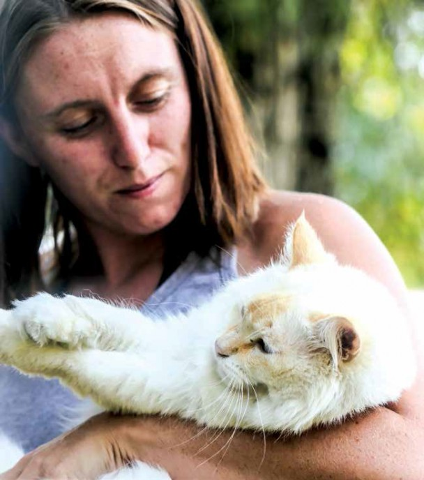 Shye Virgilio pets her pet cat after having her rescued animals taken and relocated to other shelters.