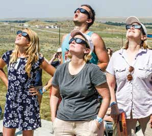 Cory Slater (back) and Signe Burke (from left) of Seattle, are joined by Michelle Champagne and Kris Moe as they watch the eclipse about 30 minutes from totality.