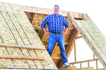 Robert Coppa stands on the open beams of his prototype as he continues to streamline his tiny house design with the hope of building a small tiny house community on his five-acre stretch of land where people can come try out simple living.